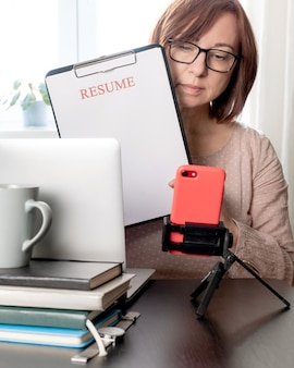 Cv d'ordinateur portable tenant femme d'âge moyen 50 ans plus l'application de feuille cv vierge au travail