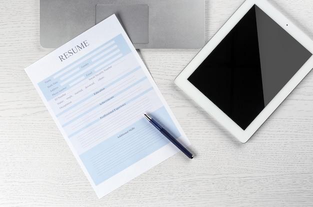 Cv, tablette et ordinateur portable sur table en bois