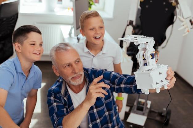 Cyber âge. mise au point sélective d'un robot moderne entre les mains d'un homme âgé joyeux