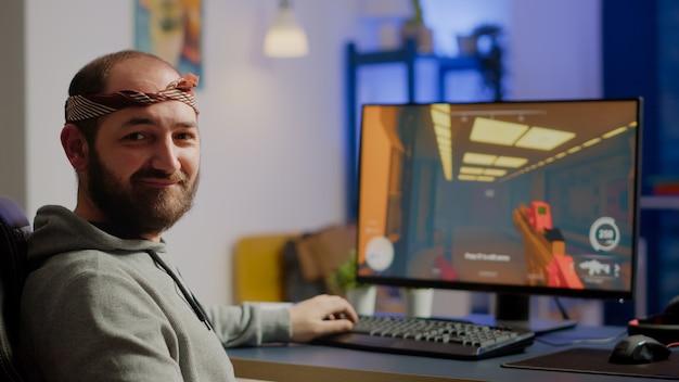 Un cyber-homme pro regardant la caméra avant de jouer à des jeux vidéo de tir spatial à l'aide d'un clavier rvb professionnel sur un ordinateur puissant. joueur professionnel jouant pendant le championnat de jeu en ligne tard dans la nuit