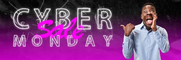 Cyber lundi, vente, concept d'achats. lettres lumineuses au néon sur fond dégradé. homme étonné appelant. espace négatif. design moderne. art contemporain. collage créatif conceptuel et coloré.