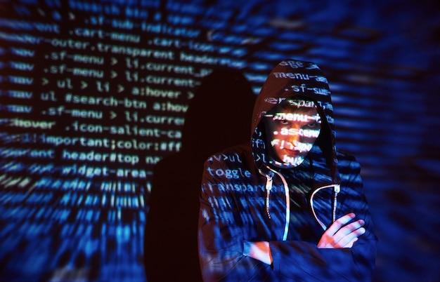 Cyberattaque avec un pirate informatique à capuche méconnaissable utilisant la réalité virtuelle, effet de pépin numérique