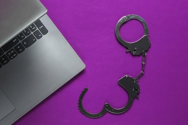 Cybercriminalité, vol numérique en ligne. ordinateur portable avec menottes en acier. vue de dessus