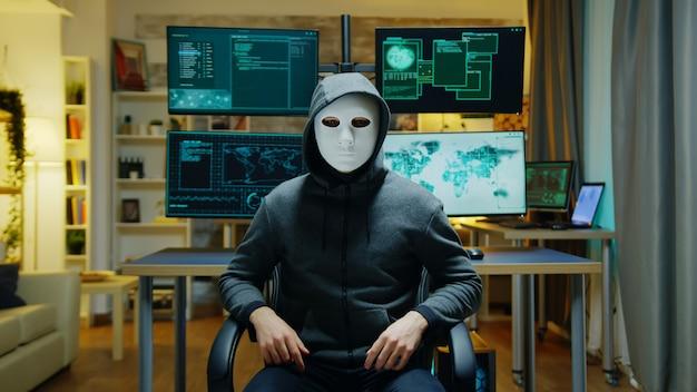 Cybercriminel portant un masque blanc utilisant la réalité augmentée pour voler des informations secrètes.