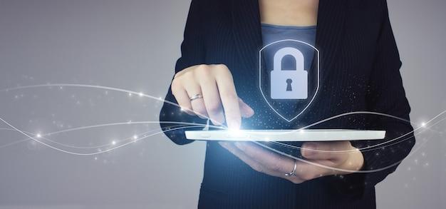 Cybersécurité, concept de criminalité numérique. tablette blanche dans la main d'une femme d'affaires avec serrure à hologramme numérique, signe d'icône de cadenas sur le dos gris. concept de confidentialité de la protection des données. rgpd. réseau de cybersécurité.