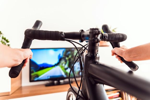 Cyclisme en salle avec entraîneur de vélo d'exercice se motivant avec la gamification du sport.