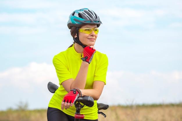 Cycliste de belle fille avec un vélo sur la nature. mode de vie sain et sport. loisirs et passe-temps