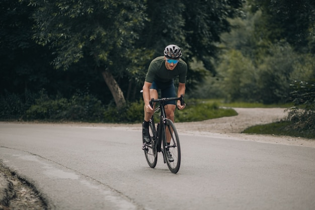 Cycliste en casque et lunettes faisant de l'exercice en forêt