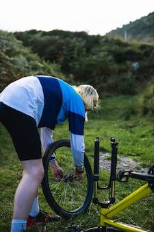 Cycliste changeant les roues de son vélo