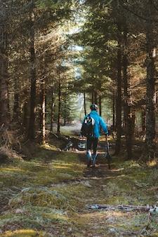 Cycliste dans un manteau bleu et un casque dans le parc avec de grands arbres