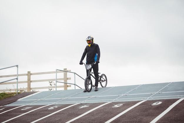 Cycliste debout avec vélo bmx sur la rampe de départ