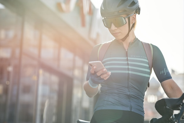 Cycliste féminine en tenue de protection à l'aide d'un smartphone tout en faisant du vélo dans le centre-ville sportive