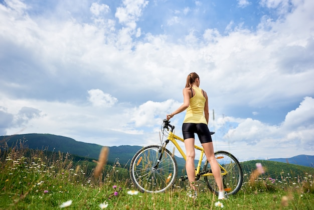 Cycliste féminine à vélo dans les montagnes