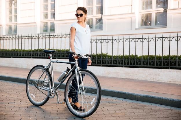 Cycliste femme brune occasionnelle debout près d'un vélo dans la rue