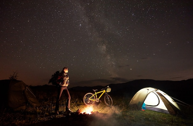 Cycliste de femme en camping de nuit près de feu de camp en feu