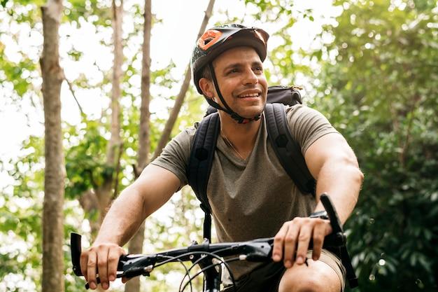 Cycliste heureux à travers la forêt