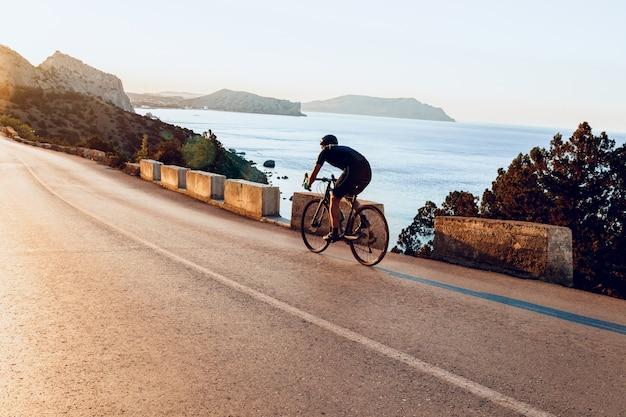 Cycliste homme pédalant sur un vélo de route à l'extérieur au coucher du soleil
