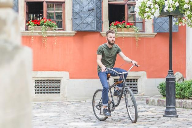 Cycliste mâle en vélo devant l'immeuble