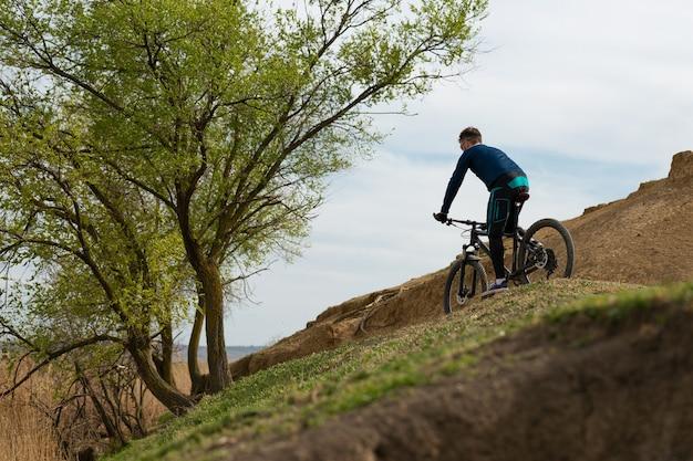 Le cycliste de montagne barbu monte les montagnes et la forêt
