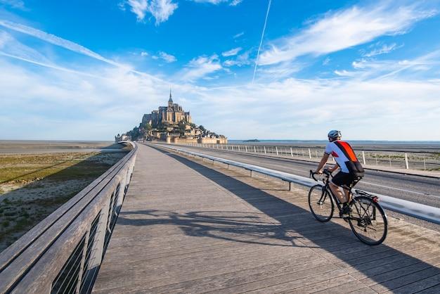 Cycliste roulant sur la seule voie d'accès au mont saint michel. le vélo est l'une des options autorisées pour l'accès