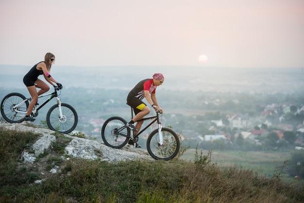 Cycliste avec sa petite amie en mouvement sur des vélos de sport sur fond de beau coucher de soleil.