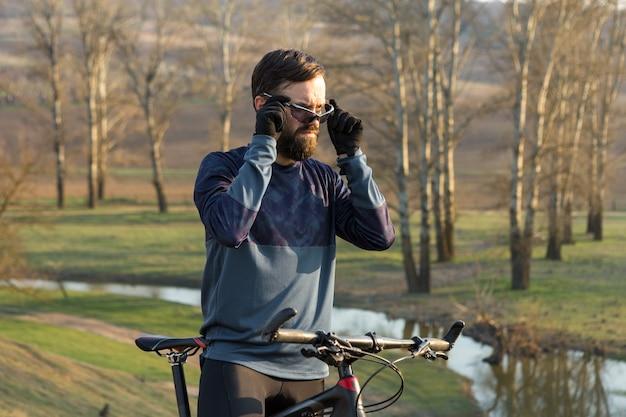 Cycliste en short et maillot sur un vélo semi-rigide moderne en carbone avec une fourche à suspension pneumatique debout sur une falaise sur fond de forêt printanière verte et fraîche