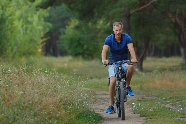 Un cycliste souriant fait du vélo dans une forêt de pins