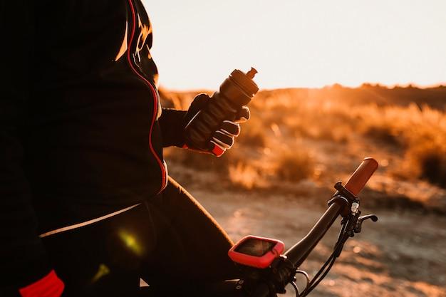 Cycliste tenant une cantine sur le vélo sur une colline rocheuse vers le bas au coucher du soleil. concept de sport extrême.