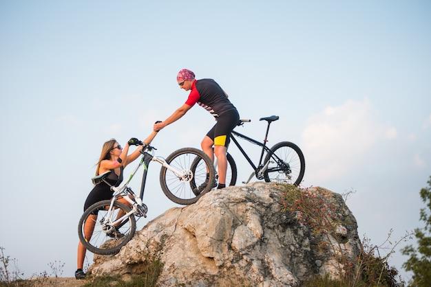 Cycliste tire la femme de la main avec un vélo de montagne dans la colline escarpée contre le ciel bleu du soir
