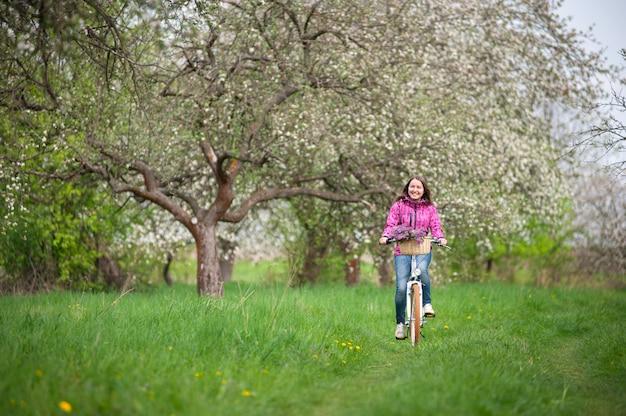 Cycliste sur un vélo blanc vintage dans un jardin de printemps