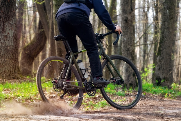 Cycliste sur un vélo de gravier. un cycliste roule le long d'un chemin forestier dérivant avec la roue arrière et augmentant le terrain.