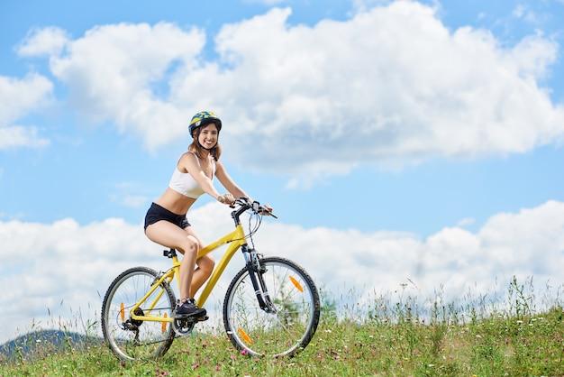 Cycliste sur vélo de montagne jaune sur l'herbe, profitant de la journée d'été contre le ciel bleu avec des nuages