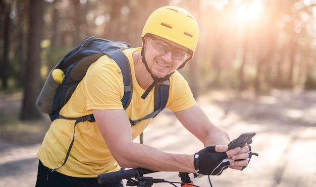 Cycliste à vélo vérifiant le navigateur gps dans le smartphone en bois de pin