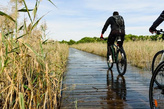 Cyclistes traversant une passerelle sur un lac inondé à valence, en espagne, par une journée ensoleillée