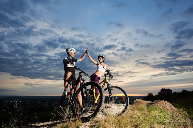Les cyclistes avec des vélos de montagne au coucher du soleil