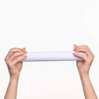 Le cylindre blanc des accessoires dans les mains féminines sur blanc avec ombre droite
