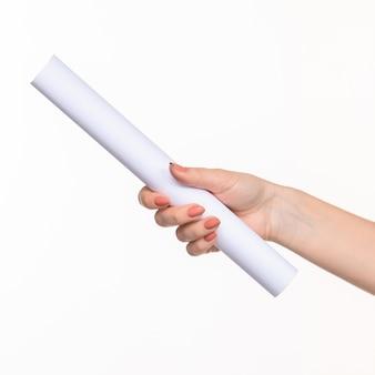 Le cylindre blanc des accessoires dans les mains féminines sur blanc