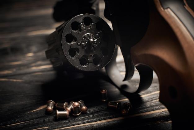 Cylindre de revolver avec munitions flobert 4mm sur fond de bois foncé