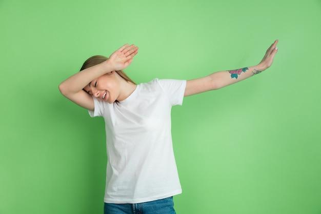 Dab du gagnant, tamponnant. portrait de jeune femme caucasienne sur mur vert. beau modèle féminin en chemise blanche. concept d'émotions humaines, expression faciale, jeunesse.