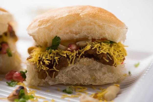 Dabeli est un snack indien servi avec des graines de grenade et de la coriandre dans une assiette en céramique blanche. c'est un aliment populaire du festival navratri