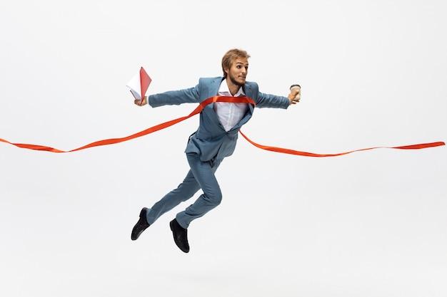 Dactylographie. homme en tenue de bureau en cours d'exécution, jogging sur un espace blanc comme athlète professionnel, sportif. look inhabituel pour homme d'affaires en mouvement, action avec ballon. sport, mode de vie sain, créativité.