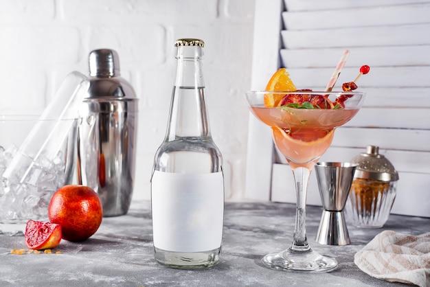 Daiquiri français, cocktail d'alcool à l'orange et au jus de pamplemousse frais avec une bouteille