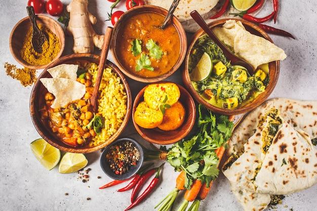 Dal, palak paneer, curry, riz, chapati, chutney dans des bols en bois sur un tableau blanc.
