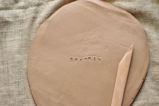 Dalle d'argile avec des outils en bois pour l'artisanat fait main avec la céramique d'impression