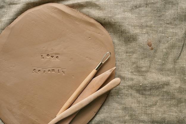 Dalle d'argile avec des outils en bois pour l'artisanat fait main avec espace de copie en céramique d'amour d'empreinte