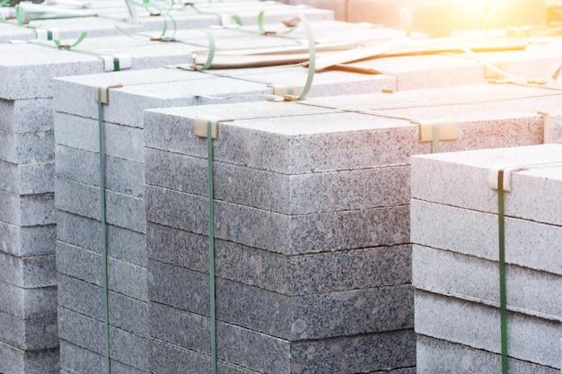 Dalles de marbre, pavés, matériaux de construction sur palettes.