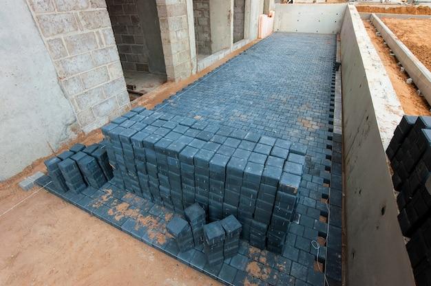 Les dalles de pavage se trouvent en rangées sur un chantier de construction en été