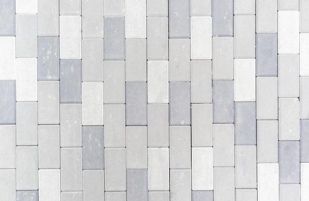 Dalles ou pierres grises nouvellement posées en béton ou pavées pour les sols ou les allées. dalles de pavage en béton dans la cour arrière ou pavage de la route. chemin de brique de jardin dans la cour sur une fondation sablonneuse.