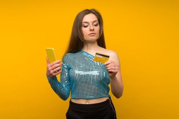 Dame acheter en ligne avec une carte de crédit et un téléphone intelligent sur fond jaune