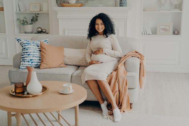 Dame adorable enceinte afro-américaine en robe longue décontractée reposant sur un canapé